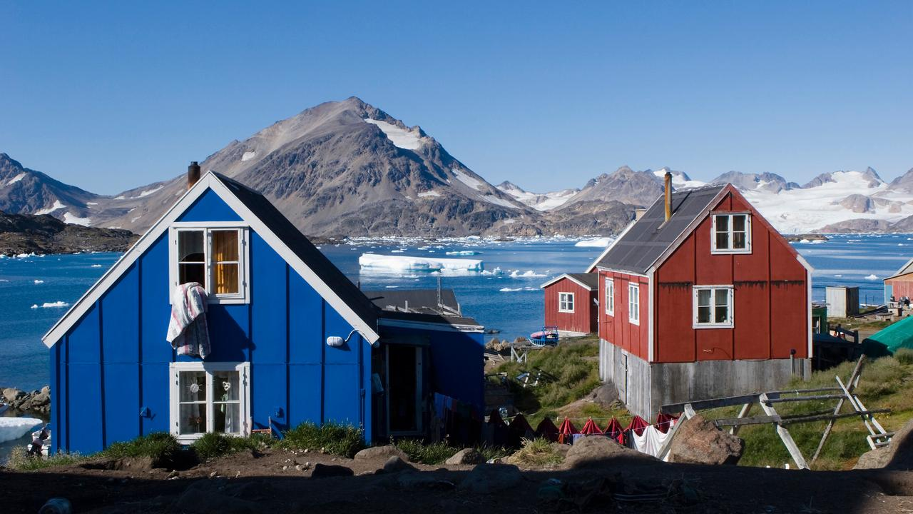 Typical Norwegian Arctic houses overlooking a Fjord with Icebergs
